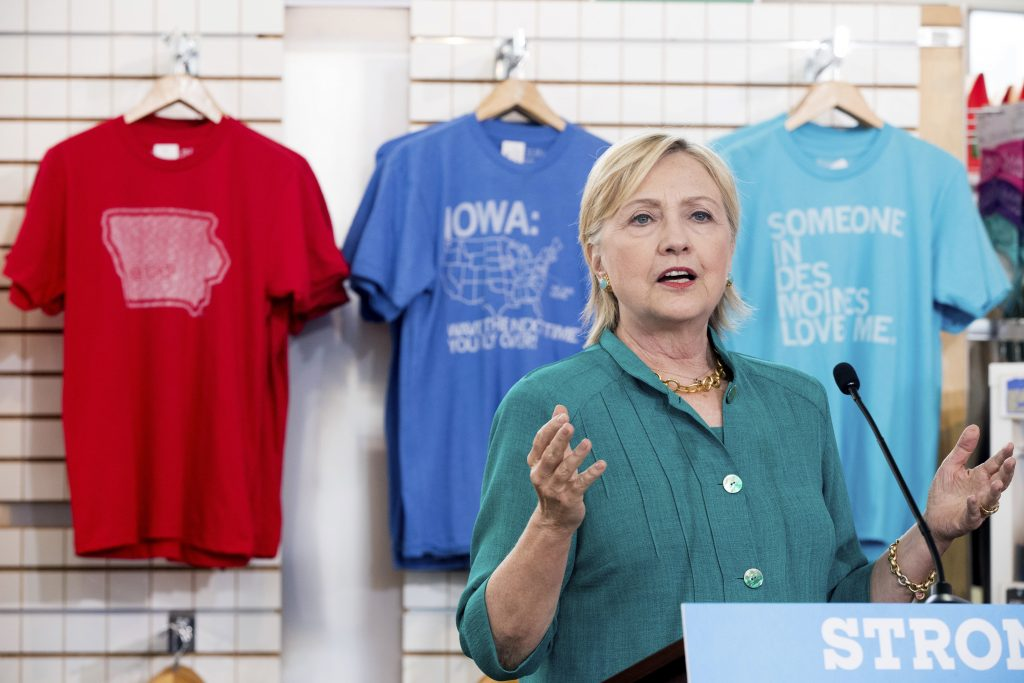 Iowa based shirts are on display behind Democratic presidential candidate Hillary Clinton as she speaks after touring Raygun, a printing, design and clothing company, in Des Moines, Iowa, Wednesday, Aug. 10, 2016. (AP Photo/Andrew Harnik)