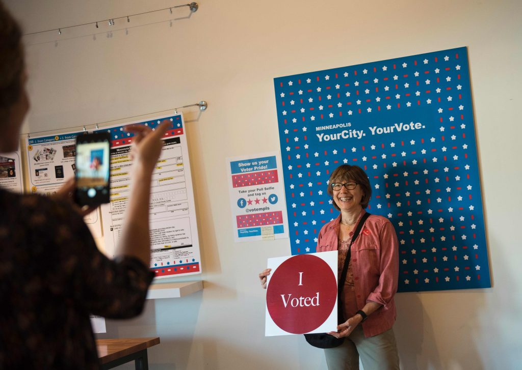 A woman gets her photo take after voting at the Early Vote Center in northeast Minneapolis, Minnesota on October 5, 2016.  Voters in Minnesota can submit their ballot for the General Election at locations across the state every day until Election Day on November 8, 2016. / AFP PHOTO / STEPHEN MATUREN