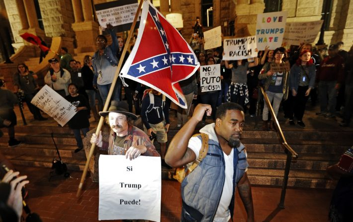 A Trump supporter with a flag, left, counter protests as Mark Hughes, right, President of the Next Generation Action Network, Tarrant County chapter leads a small group outside the courthouse protesting in opposition of President-elect Donald Trump, Friday, Nov., 11, 2016, in Fort Worth, Texas. (Brandon Wade/Star-Telegram via AP)