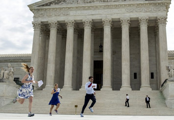 Interns with media organizations run with the decision upholding the Affordable Care Act at the Supreme Court in Washington June 25, 2015. The U.S. Supreme Court on Thursday upheld the nationwide availability of tax subsidies that are crucial to the implementation of President Barack Obama's signature healthcare law, handing a major victory to the president. REUTERS/Joshua Roberts