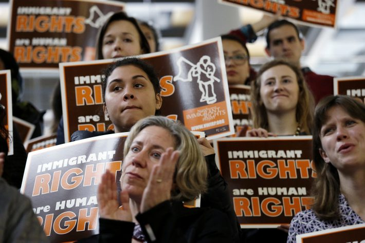 Demonstrators holding immigrant rights signs look on at a post-election event of elected officials and community leaders Wednesday, Nov. 9, 2016, at City Hall in Seattle. Seattle Mayor Ed Murray said the country had elected a leader who has