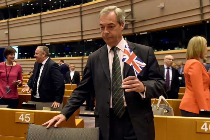 Nigel Farage, the leader of the United Kingdom Independence Party, holds the British flag as he attends a plenary session at the European Parliament on the outcome of the