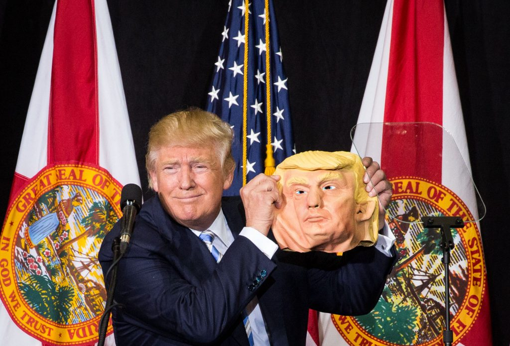 Donald Trump takes a break from speaking to compare his face to a mask during a rally at the Sarasota Fairgrounds in Sarasota, Fla., on Monday, Nov. 7, 2016. Trump spotted the mask in the crowd, and had it passed up to him. (Loren Elliott/The Tampa Bay Times via AP)