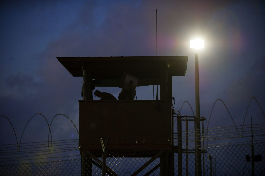 (FILES) In this March 30, 2010 file photo reviewed by US military officials, a member of the US military mans the guard post before sunrise at Camp Delta, part of the US Detention Center in Guantanamo Bay, Cuba. The White House on January 3, 2017 pledged to move ahead with the transfer of inmates out of the military prison at Guantanamo Bay, rejecting President-elect Donald Trump's demand for a freeze. With President Barack Obama set to leave office on January 20, White House spokesman Josh Earnest put Trump on notice that more inmates would be moved.
