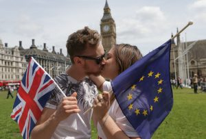 People pose kissing each other in a kiss chain organised by pro-Europe 'remain' campaigners seeking to avoid a Brexit in the EU referendum in Parliament Square in front of the Houses of Parliament in central London on June 19, 2016. / AFP PHOTO / Daniel Leal-Olivas