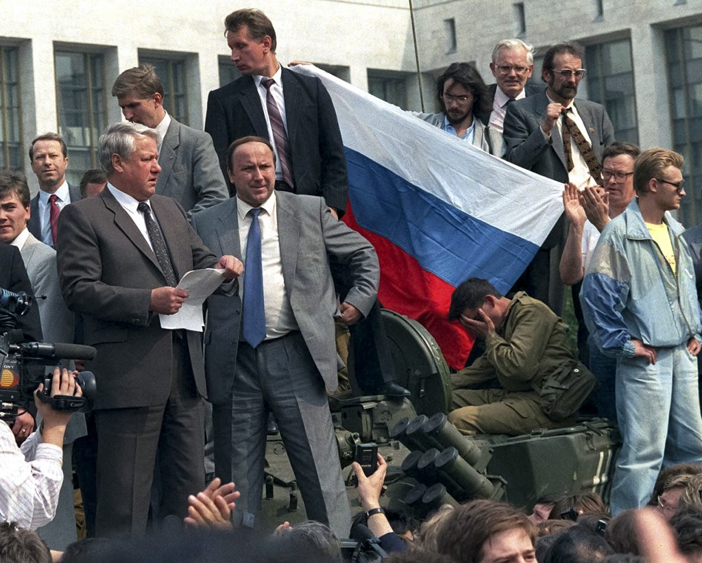 FILE - In this Aug. 19, 1991 file photo, Russian President Boris Yeltsin, foreground left, addresses the crowd standing atop of a tank in front of the Russian Government building, also known as White House, surrounded by his bodyguards, Alexander Korzhakov, center, and Viktor Zolotov, top center, in Moscow, Russia. As the 25th anniversary of the so-called August Coup draws near this Friday, The Associated Press has talked to participants and witnesses of those critical days when Muscovites turned out to defend the spirit of democracy that Gorbachev had unleashed, and many Soviet officers defied their orders and sided with the people, ensuring that that the plotters failed. (AP Photo, file)