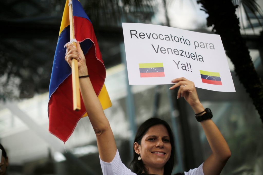 A Venezuelan living in Guatemala holds a sign during a protest to demand a referendum to remove Venezuela's President Nicolas Maduro, outside the Venezuela embassy in Guatemala City, Guatemala, September 1, 2016. The sign reads