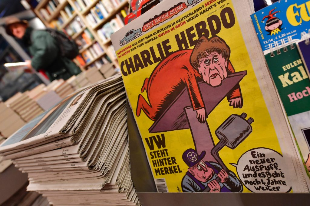 The first issues of the German version of French satirical weekly Charlie Hebdo are for sale at a newsstand in Berlin on December 1, 2016. / AFP PHOTO / John MACDOUGALL