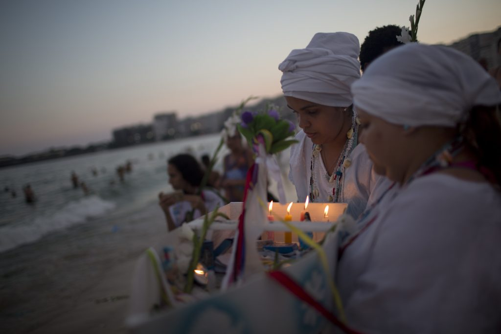 Faithful take part in a ceremony for Yemanja, goddess of the sea, that is part of traditional New Year's celebrations on Copacabana beach in Rio de Janeiro, Brazil, Thursday, Dec. 29, 2016. As the year winds down, Brazilian worshippers of Yemanja celebrate the deity, offering flowers and launching large and small boats into the ocean in exchange for blessings in the coming year. The belief in the goddess comes from the African Yoruban religion brought to America by West African slaves. (AP Photo/Silvia Izquierdo)