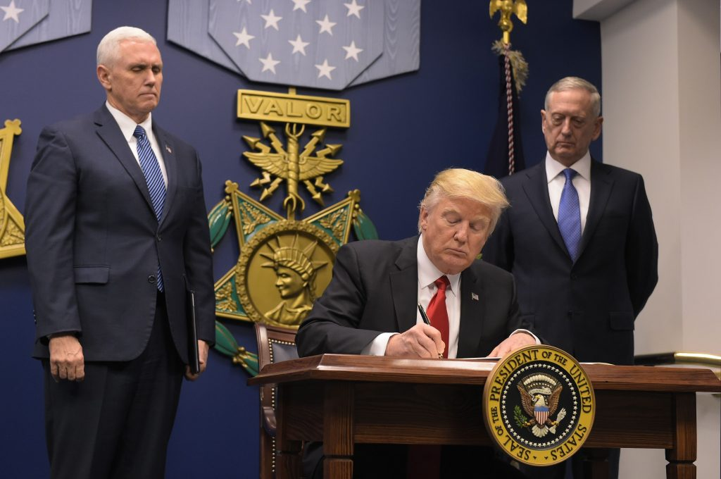 US President Donald Trump signs an executive order alongside US Defense Secretary James Mattis and US Vice President Muike Pence on January 27, 2016 at the Pentagon in Washington, DC. Trump signed an order Friday to begin what he called a