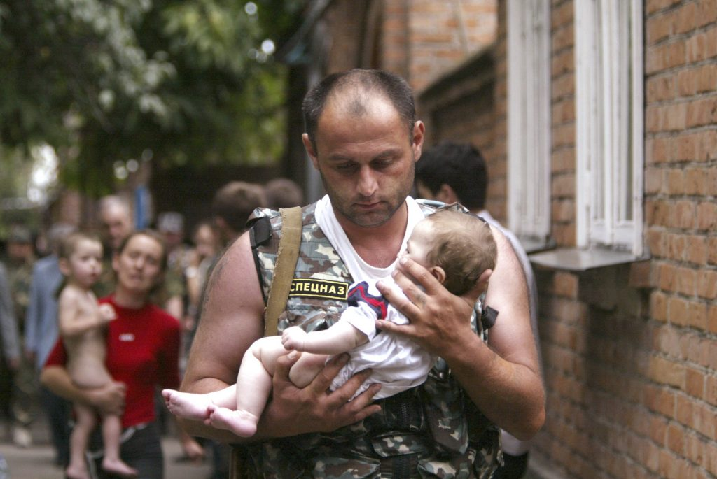 REUTERS PICTURES OF THE DECADE. A Russian police officer carries a released baby from the school seized by heavily armed masked men and women in the town of Beslan in the province of North Ossetia near Chechnya, September 2, 2004. An armed gang, holding hundreds of people hostage in a Russian school, on Thursday freed four infants and at least two women. REUTERS/Viktor Korotayev (RUSSIA)